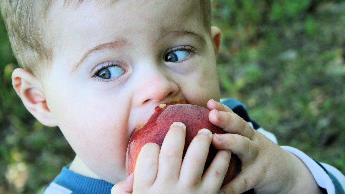 boy eating peach