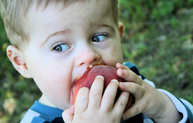 boy eating peach